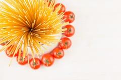 Składnika Włoskiego makaronu odgórny widok - snop spaghetti, czereśniowi pomidory, basil, ser na białej drewno desce z pustą kopi Zdjęcia Royalty Free