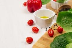 Składniki dla gotować świeżej surowej wiosny sałatki zieleni i czerwoni warzywa, pikantność, olej z drewnianym kitchenware na bia Zdjęcia Stock