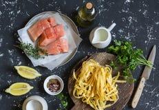 Składniki dla gotować lunch surowy łosoś, suchy makaronu tagliatelle, śmietanka, oliwa z oliwek, pikantność i ziele -, Na ciemnym Obraz Stock