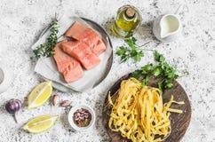 Składniki dla gotować lunch surowy łosoś, suchy makaronu tagliatelle, śmietanka, oliwa z oliwek, pikantność i ziele -, Na lekkim  zdjęcia royalty free