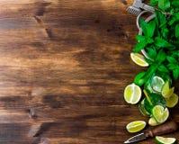 Składniki dla koktajlu - wapno, rum, nowi liście, kostki lodu na drewnianym stole Uwalnia przestrzeń dla teksta Obrazy Stock