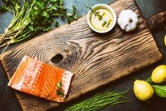 Składniki dla kucharstwa Surowy łosoś polędwicowy, asparagus i ziele na drewnianej desce, Karmowy kulinarny tło z kopii przestrze Fotografia Stock