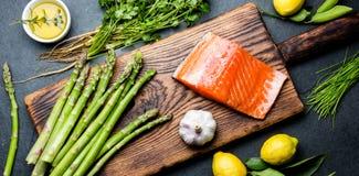 Składniki dla kucharstwa Surowy łosoś polędwicowy, asparagus i ziele na drewnianej desce, Karmowy kulinarny tło z kopii przestrze Fotografia Royalty Free