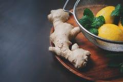 Składniki dla kulinarnego imbiru, mennicy i cytryny gorącej herbaty, lemoniady na drewnianym talerzu w ciemnym nieociosanym wnętr zdjęcia royalty free