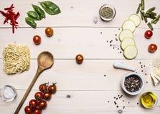 Składniki dla kulinarnego jarskiego jedzenia, czereśniowi pomidory, basil, zucchini, moździerza pieprz, olej, drewniana łyżka, kł Fotografia Royalty Free