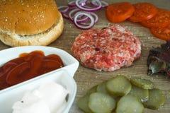 Składniki dla kulinarnych hamburgerów Surowi zmieloni mięśni cutlets na drewnianym tle, czerwona cebula, pomidory, zielenie, zale Fotografia Stock