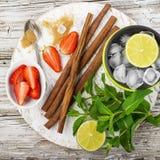Składniki dla odświeżającego lata witaminy zdrowych napojów: wapno, mennica, jagody, owoc, lód, brown cukier, cynamonowi kije Fotografia Stock