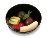 Składniki dla owocowej sałatki w czarnym ceramicznym pucharze odizolowywającym Zdjęcie Royalty Free