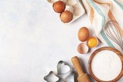 Składniki dla piec - mąka, drewniana łyżka, jajka Zdjęcia Stock