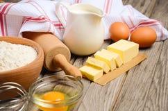 Składniki dla piec - mleko, masło, jajka i mąka, fotografia stock
