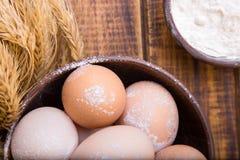 Składniki dla piekarni Świezi jajka w pucharze, banatce i mące na drewnianym tle brown, Odgórny widok Zdjęcia Stock