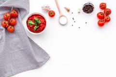 Składniki dla pomidorowego kumberlandu Czereśniowi pomidory, czosnek, zielony basil, czarny pieprz, sól w łyżce na białym tło wie Zdjęcie Stock