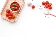 Składniki dla pomidorowego kumberlandu Czereśniowi pomidory, czosnek, zielony basil, czarny pieprz, sól w łyżce na białym tło wie Fotografia Royalty Free