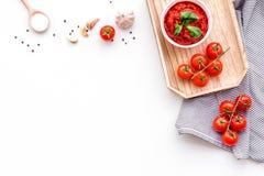 Składniki dla pomidorowego kumberlandu Czereśniowi pomidory, czosnek, zielony basil, czarny pieprz, sól w łyżce na białym tło wie Fotografia Stock