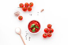 Składniki dla pomidorowego kumberlandu Czereśniowi pomidory, czosnek, zielony basil, czarny pieprz, sól w łyżce na białym tło wie Zdjęcia Royalty Free