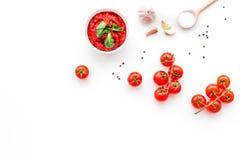 Składniki dla pomidorowego kumberlandu Czereśniowi pomidory, czosnek, zielony basil, czarny pieprz, sól w łyżce na białym tło wie Obrazy Stock