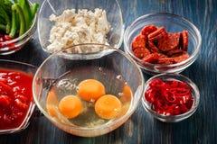 Składniki dla przygotowywać frittata jajka, kiełbasiany chorizo, czerwony pieprz, zielony pieprz, pomidory, chili i ser na drewni Zdjęcie Royalty Free