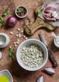 Składniki dla robić bobowej brei z bekonem białe fasole, bekon, czerwona cebula, pikantność i ziele -, - Na kamiennym tle Zdjęcie Stock