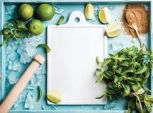 Składniki dla robić mojito lata koktajlowi: odłupany lód, nowi liście, brown cukier i wapno na turkusowym błękicie malującym, Obraz Stock