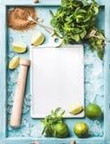 Składniki dla robić mojito lata koktajlowi: odłupany lód, nowi liście, brown cukier i wapno na turkusowym błękicie malującym, Zdjęcia Stock