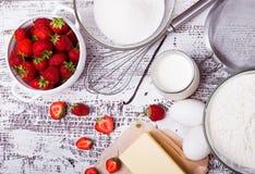 Składniki dla robić truskawkowemu jogurtu tortowi na białych drewnianych półdupkach Zdjęcie Royalty Free