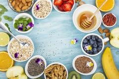 Składniki dla zdrowego śniadania, dokrętki, oatmeal, miód, jagody, owoc, czarna jagoda, pomarańcze, Jadalni kwiaty, Chia Zdjęcie Stock