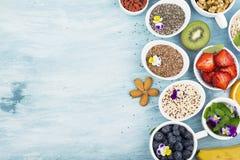 Składniki dla zdrowego śniadania, dokrętki, oatmeal, miód, jagody, owoc, czarna jagoda, pomarańcze, Jadalni kwiaty, Chia Fotografia Stock