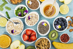 Składniki dla zdrowego śniadania, dokrętki, oatmeal, miód, jagody, owoc, czarna jagoda, pomarańcze, Jadalni kwiaty, Chia Obraz Stock