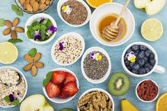 Składniki dla zdrowego śniadania, dokrętki, oatmeal, miód, jagody, owoc, czarna jagoda, pomarańcze, Jadalni kwiaty, Chia Zdjęcia Stock