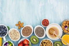 Składniki dla zdrowego śniadania, dokrętki, oatmeal, miód, jagody, owoc, czarna jagoda, pomarańcze, Jadalni kwiaty, Chia Zdjęcie Royalty Free