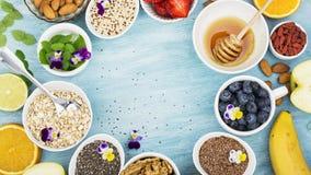 Składniki dla zdrowego śniadania, dokrętki, oatmeal, miód, jagody, owoc, czarna jagoda, pomarańcze, Jadalni kwiaty, Chia Zdjęcia Royalty Free