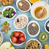 Składniki dla zdrowego śniadania, dokrętki, oatmeal, miód, jagody, owoc, czarna jagoda, pomarańcze, Jadalni kwiaty, Chia Fotografia Royalty Free