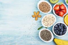 Składniki dla zdrowego śniadania, dokrętki, oatmeal, miód, jagody, owoc, czarna jagoda, pomarańcze, Jadalni kwiaty, Chia Obraz Royalty Free