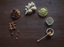 Składniki na brown stole dla piec używa miód, imbir, cynamon, cloves, suszyli - owocowych i konopianych ziarna zdjęcia stock