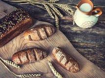 Składu czarny chleb na desce, rocznika nóż, mleko, pszeniczni płatki, dokrętki na stołowym i starym tle, pojęcie uzdrawia zdjęcia stock