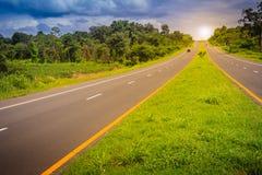 Skłon autostrada z światła słonecznego i zieleni ruchu drogowego wyspą Cztery pas ruchu Fotografia Stock