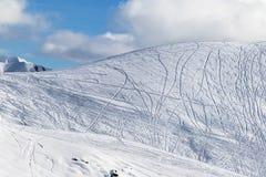 Skłon dla freeriding z śladami od nart, snowboards i błękita, Fotografia Stock