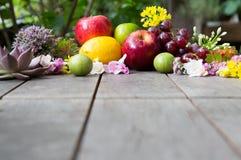 Skład owoc i kwiaty na drewno stole Fotografia Royalty Free