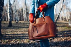 Sk?nhet och danar Stilfull trendig kvinna som bär den ljusa klänningen som rymmer den bruna påsehandväskan royaltyfria foton