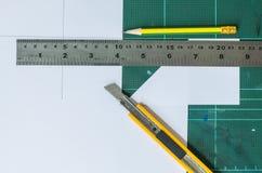 Sk?rare, tr?blyertspenna och linjal p? gammal gr?n bakgrund f?r gummiblock arkivbilder