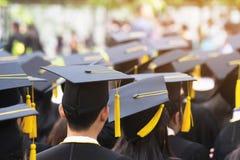 Sk?t av avl?ggande av examenhattar under avslutningframg?ngkandidater av universitetet royaltyfria bilder