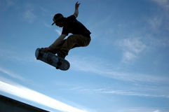 Sk8tr blue sky air. Silhouette of teen male skateboarder in mid flight against blue sky with clouds Royalty Free Stock Photos