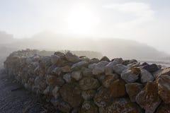 Skała Brukujący ogrodzenie w mgle fotografia stock