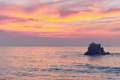 Skała przy zmierzchem na morzu z różowymi kolorami Obrazy Stock