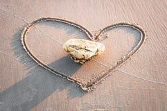 Skała w kierowym ostrzu rysuje ręką w piasku Zdjęcia Stock
