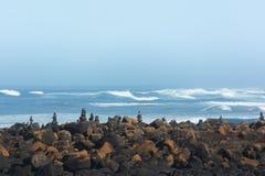 Skały balansuje w stercie na kamieniu zakrywali plażę z oceanem behind Obraz Royalty Free