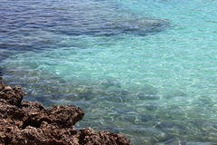 Skały i błękitny cristal morze Obrazy Royalty Free