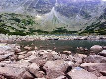Skały i kamienie na wysokiej góry jeziorze wyrzucać na brzeg Obrazy Stock