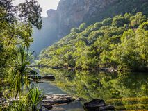 Skały i zielony warkocz odbija jasno wodę przed dramatyczną falezy twarzą obrazy stock