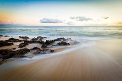 Skały na plaży przy zmierzchem Zdjęcia Royalty Free